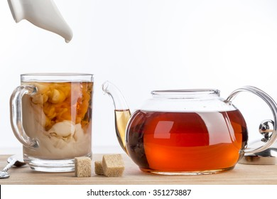 Dissolve milk in a cup of black tea. Transparent teapot and cup with three cubes of brown sugar