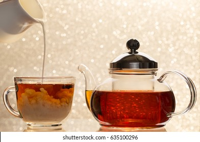 Dissolve milk in a cup of black tea. Transparent teapot and cup