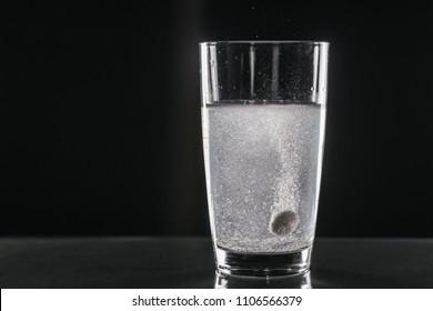 dissolving effervescent tablet. On black background