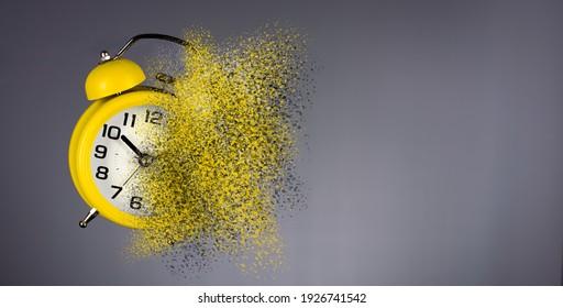 Dissolving yellow alarm clock. Dissolving time