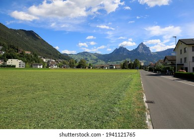 In the distance, behind the grassy land, a mountain range with two rocky peaks is seen. This is seen here in Brunnen in the canton of Schwyz in Switzerland.