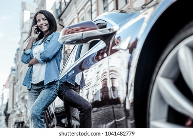 Distance communication. Positive nice happy woman leaning on her car and smiling while talking on the phone