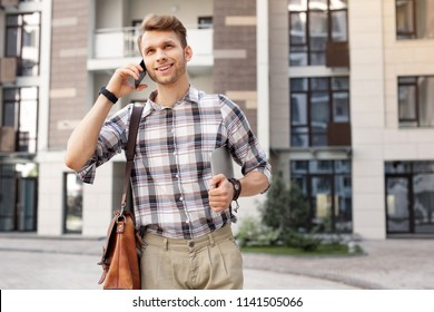 Distance connection. Joyful good looking man putting a phone to his ear while making a call