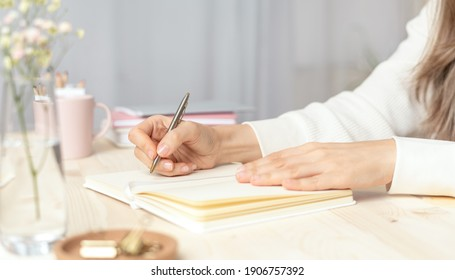 Distance learning, education and work. Woman hand holding pen on notepad at home, writes goals, plans, make to do and wish list on desk, working from home office.