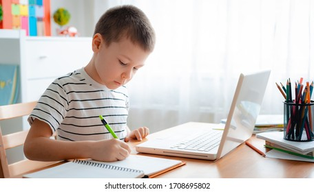 Distance learning online education. A schoolboy boy studies at home and does school homework. A home distance learning.