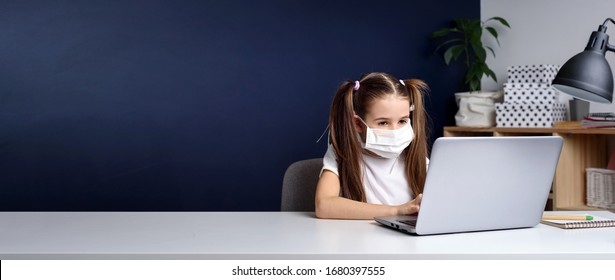 Distance learning online education. schoolgirl in medical mask studying at home, working at laptop notebook and doing school homework. covid quarantine.