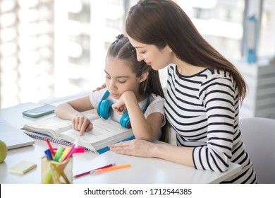 Distance learning. School girl with headphones reading a textbook and caring mom hugging her shoulder.