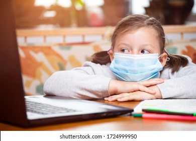 Distance learning-online education. School girl with face mask watching online education classes and doing school homework. COVID-19 pandemic forces children online learning. - Shutterstock ID 1724999950
