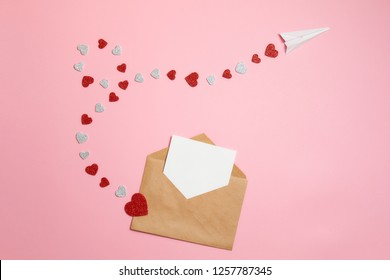 Distance love concept, sending love letter, valentines day. Kraft envelope with blank postcard and paper airplane flying on route made of heart shaped valentines cards lay on pink background desk