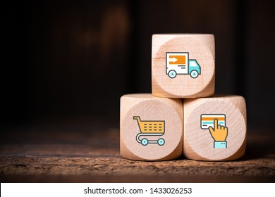 Distance or online shopping concept with three wooden blocks showing icons for a shopping cart, card for payment and delivery truck with lateral copy space