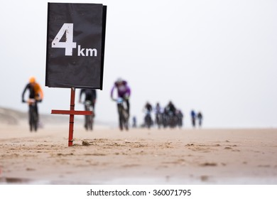 a distance sign which says that mountain bike race participants are four kilometer away from the finish during a beach race.