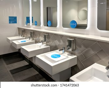 Distance stickers and signs fixed over the sinks, mirrors in a public toilet for the people to follow social distancing to avoid infection of coronavirus disease.