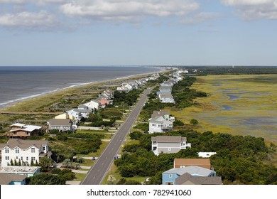Distant aerial view of Oak Island, NC coastal living homes road, marsh and more in the summer. Day high view of homes and more at Atlantic coasts Oak Island.