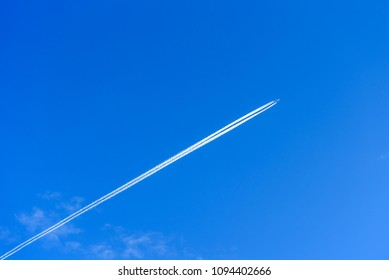 A distant aircraft with long diagonal condensation trails or contrails on a blue sky day
