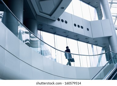 Distant businessman walking in modern office building