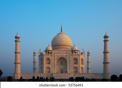 Distant and compressed with telephoto, the symmetrical and centered Taj Mahal is glowing colorful red dawn sunrise colors on a clear blue sky morning in Agra, India. Horizontal copy space