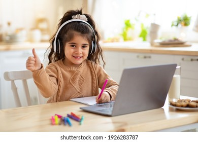 Distant Education. Adorable Little Girl In Headphones Using Laptop In Kitchen, Sitting At Table And Showing Thumb Up At Camera, Female Child Study Online With Computer And Drawing With Pencils