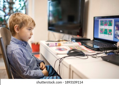 Distant education, online class meeting. Preschool boy in formal shirt but in pajama trousers studying during online lesson at home, social distance during quarantine, self-isolation