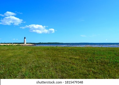 The distant Gladstone Michigan lighthouse on the Green Bay with blue clouded sky above.  The long large park lawn area is in the foreground balancing the image out to the horizon on Lake Michigan. - Shutterstock ID 1815479348