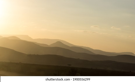Distant hazy mountains, colored different shades of pink and grey by the setting sun, in the Great Escarpment of South Africa - Shutterstock ID 1900556299