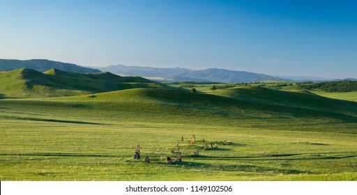 Distant hills. Hilly steppe. Curvy hills. Dolmens. Ancient gravestone. Blue sky and grass. Beautiful plain. Sunny day and hills. Lowland. Hilly horizon.