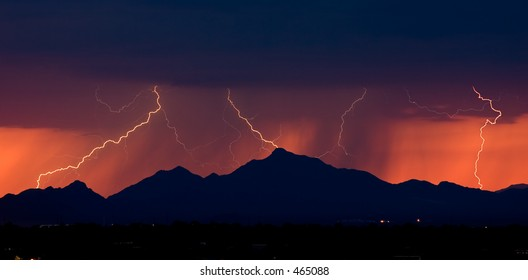 Distant lightning, made yellow by atmospheric dispersion of blue component, set against a vivid red sunset
