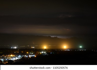 A distant lightning storm illuminates the skyline at Portsmouth in the UK, with Whitecliff Bay holiday park in the foreground. Ships lights can be seen in the Solent channel stretch of water.
