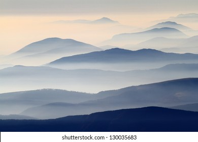 Distant mountain range and thin layer of clouds on the valleys, Romania