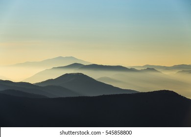 Distant mountain range and thin layer of clouds on the valleys - Misty mountains in the morning