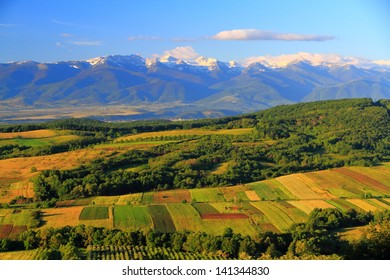 Distant mountains behind green hills under morning light