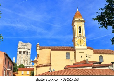 Distant runs of the Trophy of Augustus and sunny church building in Le Turbie, French Riviera, France