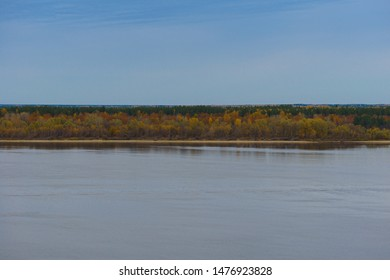 Distant sandy riverbank with autumn forest on a cloudy afternoon