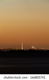 Distant skyline of Auckland City, New Zealand, with Sky Tower illuminated in twilight dusk after sunset
