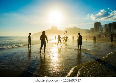 Distant sunset silhouettes playing keepy-uppie beach football on the sea shore in Ipanema Beach Rio de Janeiro Brazil