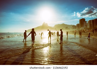 Distant sunset silhouettes of unrecognizable people playing keepy-uppie beach football on the sea shore in Ipanema Beach Rio de Janeiro Brazil