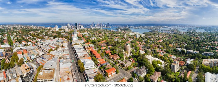 Distant Sydney city CBD and North Sydney on shores of Harbour in wide aerial panorama from residential local lower north shore suburb Crows Nest on a sunny day.