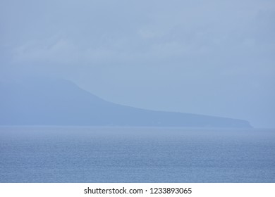 Distant unclear shape of Little Barrier Island off coast of New Zealand blending with ocean surface on hazy day.