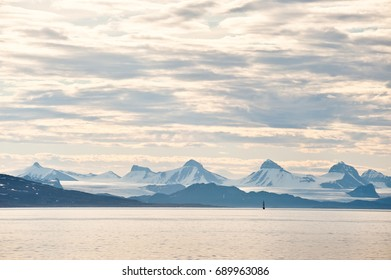 Distant view of Arctic mountains and glaciers on the east coast of Spitsbergen, dwarfing a sailing ship. Taken in the early hours of the morning in July, with continuous daylight.