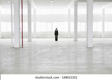Distant view of businesswoman standing in empty warehouse
