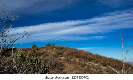 Distant view of hikers on sagebrush mountain side with blue sky and white clouds