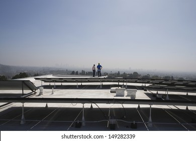 Distant view of maintenance workers near solar panels on rooftop in Los Angeles; California
