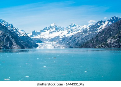 A distant view of Margerie Glacier, Alaska.  Icebergs from the glacier are floating on the water surface in the foreground and snow capped mountains in the background.