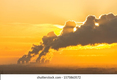 Distant view of a Power Station's cooling towers near Drax in North Yorkshire with the sun setting behind the water vapour trail on a cold winter's night. Horizontal.  Space for copy.