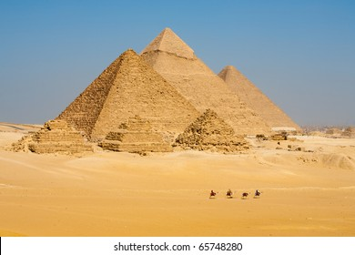 A distant view of a row of tourist camels walking in front of all of the Egyptian Giza Pyramids together in Cairo, Egypt. Horizontal copy space