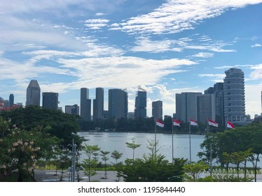 Distant view of Singapore CBD area under cloudy sky, with Singapore flags seen flying