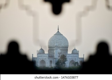 Distant view of the Taj Mahal at sunset from behind a fence