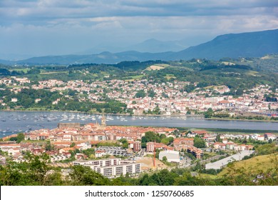 Distant view of typicall fishermen village of Hondarribia, and Henday in the Basque Country, Spain. With some small fishing boats on the foreground and the medieval tower bell on the background