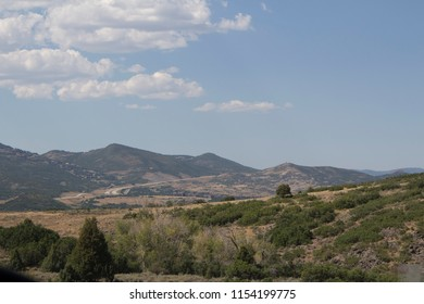 Distant view of Utah mountains on a sunny day with blue skies and white clouds