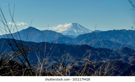 A distant winter view of Mount Fuji amongst the surrounding hills