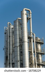 Distillation columns at industrial plant or refinery against deep blue sky